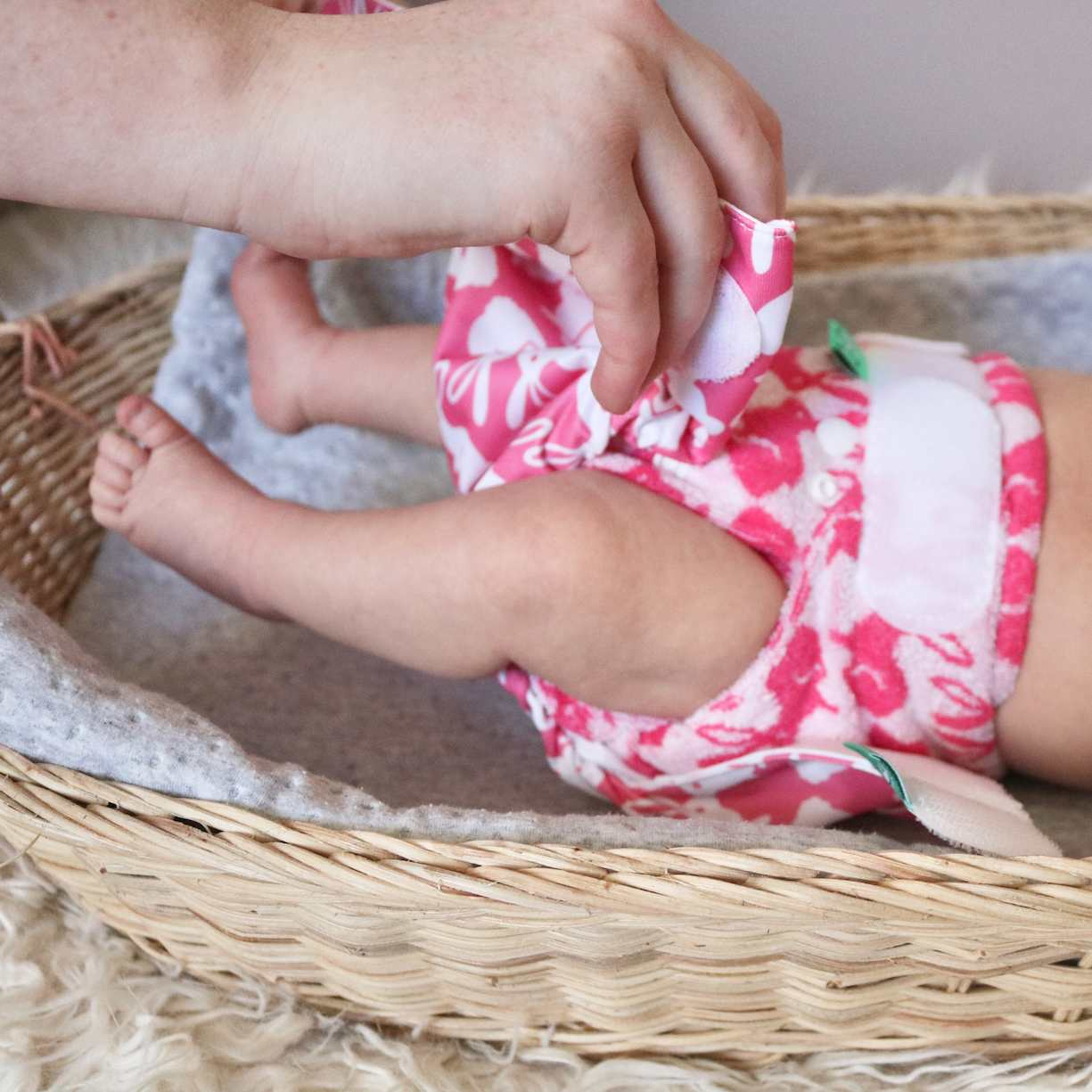 Parent putting on Reusable Nappy pink and white pattern in changing basket with blanket