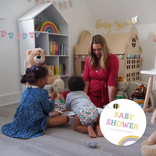 Pamella from Latte and Lullabies in playroom baby shower scene with wooden scandi playhouse in background children wearing sustainable resuable nappies and parent sat watching