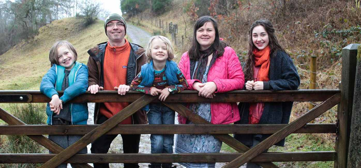 totsbots-founders-family-picture-in-woodland-two-adults-three-children-leaning-on-gate