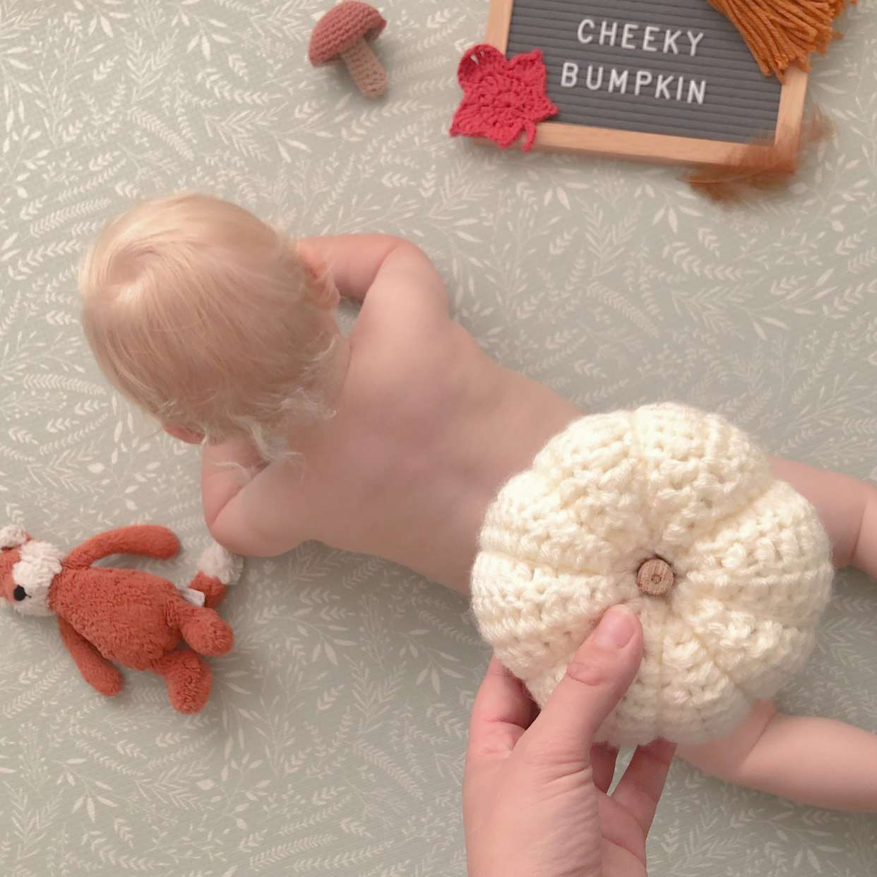 get-crafty-this-halloween-blog-baby-lying-on-front-knitted-pumpkin-on-top